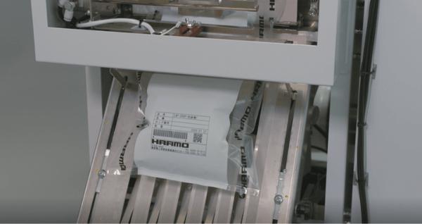 射出成形品の自動包装で、袋詰め工程の省人化と精度向上を実現